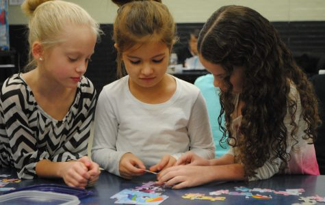 Doing a puzzle during morning hours of Metro, Fourth grader Mikayla Smith, Kindergartner Harmony Cook, and First grader Riley Gibson.